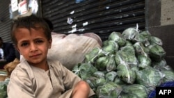A Yemeni boy sits next to bags of qat, a mild natural narcotic widely used in Yemen, as antigovernment demonstrators protest against President Ali Abdullah Saleh nearby in Sanaa on May 29.