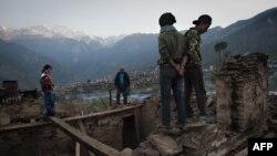 Жители одного из селений в Непале стоят на руинах одного из домов селения, 4 мая 2015 года.