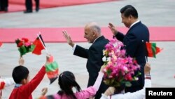 Afghan President Ashraf Ghani and Chinese President Xi Jinping (R) wave to students outside the Great Hall of the People, in Beijing, October 2014.
