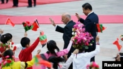 Afghanistan's President Ashraf Ghani Ahmadzai and China's President Xi Jinping (R) wave to students during a welcoming ceremony outside in Beijing, October 2014.