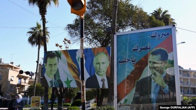 """Башар Асад, Владимир Путин және Иранды жақтайтын """"Хезболла"""" тобының басшысы Хасан Насралланың портреттері. Сирияның солтүстігіндегі Алеппо қаласы. 17 наурыз, 2018 жыл."""
