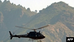 A Pakistani Frontier Corps helicopter flies over monitors the Taliban in the Umar Abad area outside the Buner district. Some 50,000 residents have fled the area due to recent fighting.