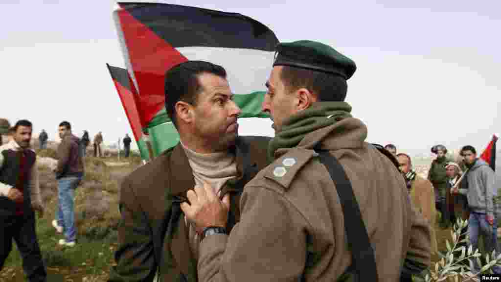 A Palestinian activist (left) argues with an Israeli border guard during a protest in the West Bank village of al-Janiya near Ramallah on February 8 (REUTERS/Mohamad Torokman)