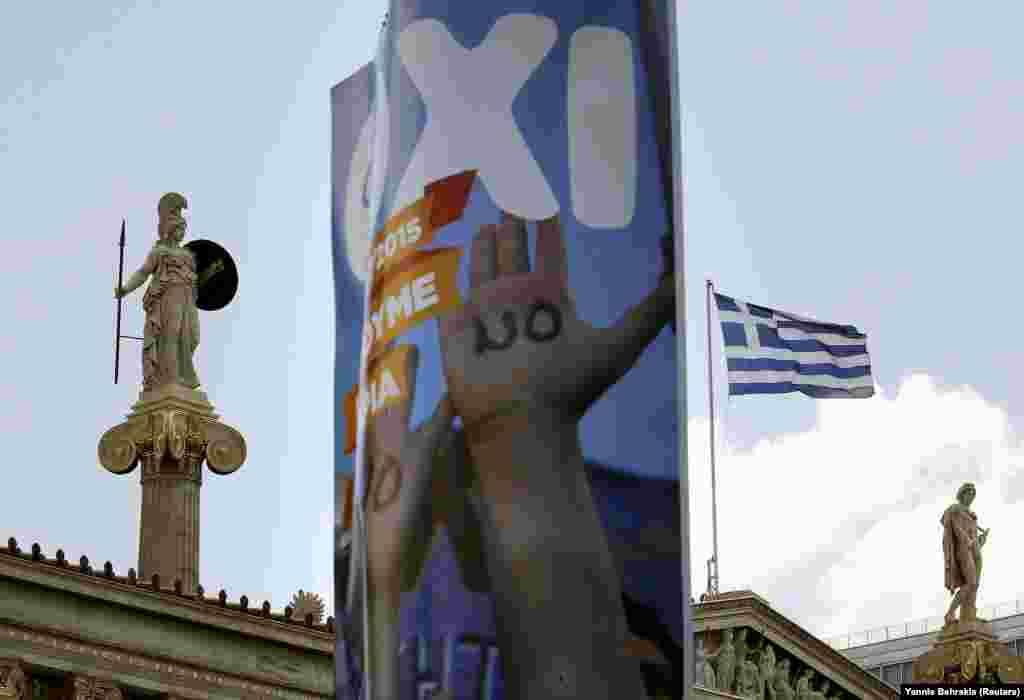 """Плакат противников сотрудничества с кредиторами с надписью """"НЕТ"""" на фоне статуи богини Афины Паллады у здания Афинской академии."""