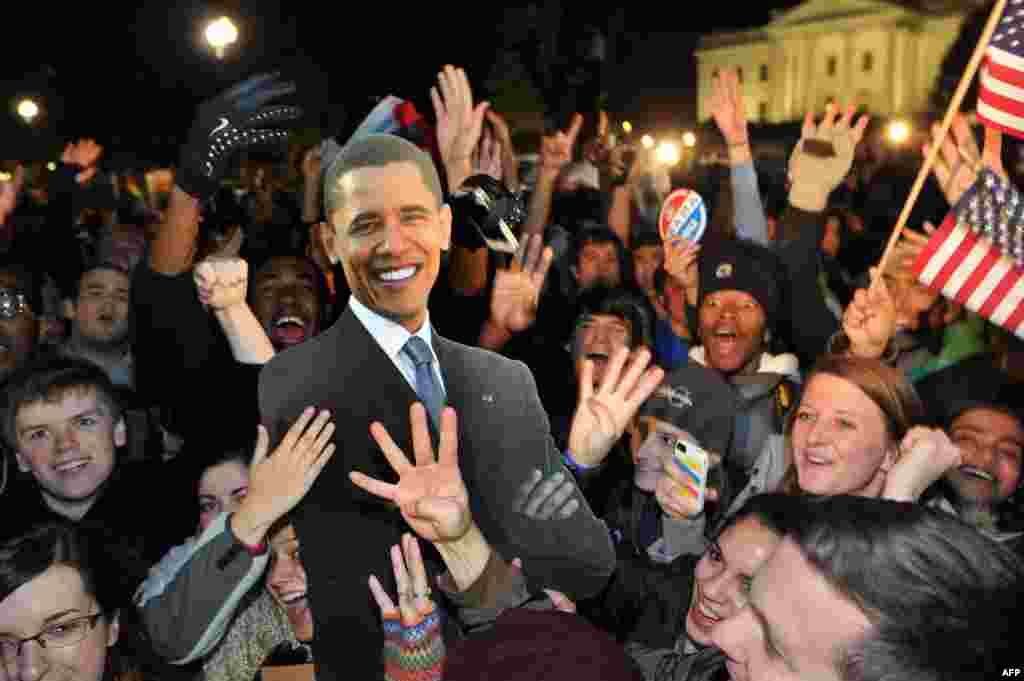 People celebrate in front of the White House in Washington after television networks announced the reelection of U.S. President Barack Obama.