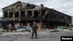Бойовик угруповання «ДНР» біля заводу, зруйнованого внаслідок бойових дій, Нижня Кринка, 23 серпня 2014 року