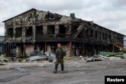 Пророссийский боевик идет у здания разрушенного из-за боёв здания фабрики. Нижняя Кринка, 23 сентября 2014 года.