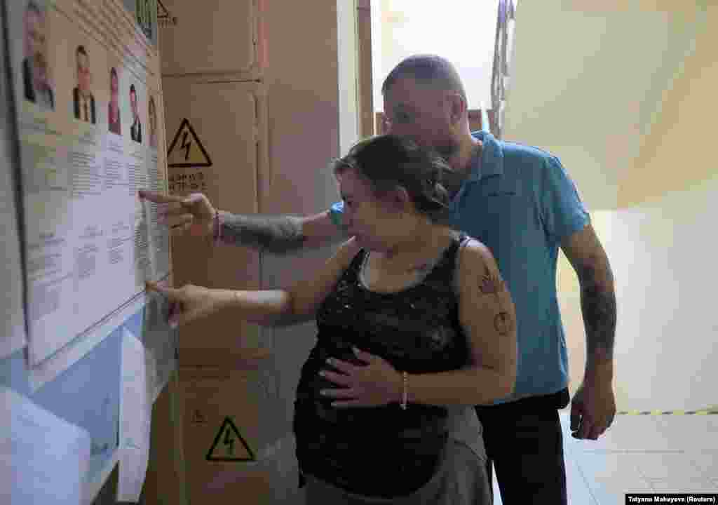 Voters study a candidate information board at a polling station in Moscow.