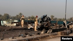 Iraq -- Security forces inspect the site of a car bomb attack on al-Muthna bridge at Taji, north of Baghdad, March 26, 2014