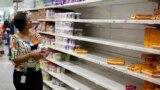 Venezuela -- A woman picks up groceries at a supermarket in Caracas August 21, 2014