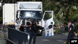 France - Forensics officers and policemen look for evidences in a truck on the Promenade des Anglais seafront in the French Riviera town of Nice on July 15, 2016, after it drove into a crowd watching a fireworks display.