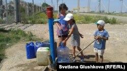 Астананың шетіндегі Өндіріс кентінде су алып жатқан балалар. 24 маусым 2014 жыл.