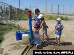 Су тасып жүрген Өндіріс ауылының балалары. Астана, 24 маусым 2014 жыл.