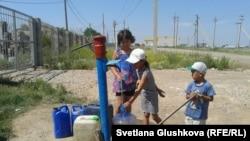 Дети набирают воду из колонки на окраине поселка Ондирис. Астана, 24 июня 2014 года.