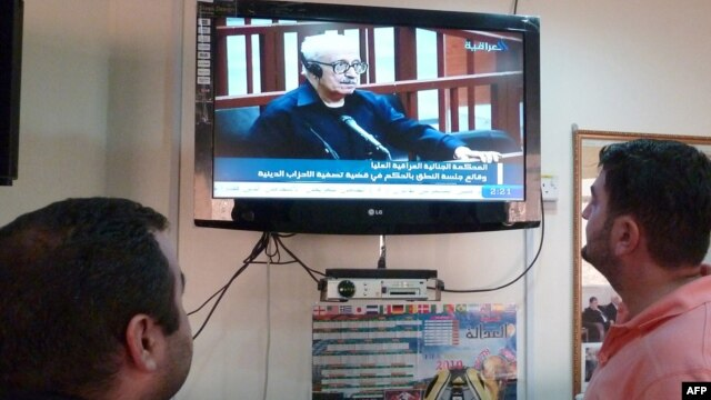 Iraqis watch a state television broadcast in Baghdad in 2010.