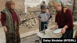 Умида моет рис в раковине на территории своего дома, сожженного во время беспорядков в июне этого года. Кыргызстан, Ош, 30 октября 2010 года.
