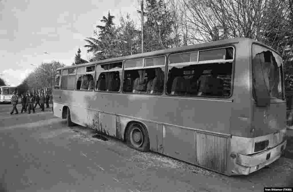 """Egy kiégett busz Dél-Oszétia fővárosában, Chinvaliban 1990 novemberében.Miután Dél-Oszétia kihirdette függetlenségétTbiliszitől,Gamszahurdia azt sürgette, hogy """"minden fegyverképes grúz csatlakozzon aChinvali elleni menethez! A roham november 23-án kezdődik!"""". Az ezt követő összecsapásokban legkevesebb hatan vesztették életüket."""