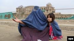 Maşgaladaky zorlugyň pidasy bolan 29 ýaşly zenan öz gyzy bilen dilegçilik edýär, Kabul, 23-nji noýabr, 2013.