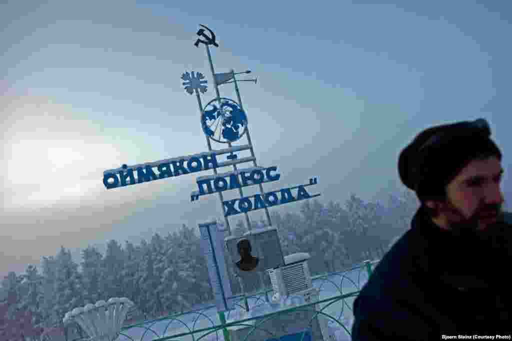 "A visitor at ""The Pole of Cold"" marker in the village of Oymyakon"