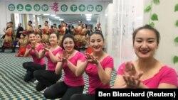 """Қытай билігінің ұйымдастыруымен барған шетелдік журналистердің алдында билеп жүрген Хотандағы """"кәсіби білім орталығындағы"""" адамдар. Шыңжаң, Қытай, 5 қаңтар 2019 жыл."""