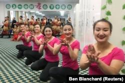 Обитательницы «образовательного центра» в Хотане танцуют для делегации иностранных журналистов, Синьцзян, 5 января 2019 года.