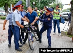 Police detain a man on a bicycle in Almaty. June 10, 2019