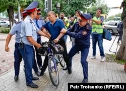 Полиция задерживает мужчину на велосипеде в центре Алматы, где ожидался несанкционированный митинг. 10 июня 2019 года.