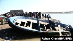 Pilgrims wait beside a boat after it capsized while carrying pilgrims to the shrine of Saint Moy Pithi, in Gharo, near Thatta on December 7.