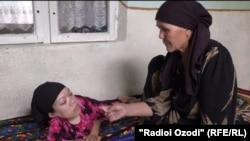 Тошбӣ Ҷавракова се фарзанди маъюбро нигоҳубин мекунад.