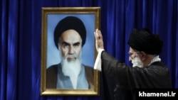 Iran -- Iran's Supreme Leader Ali Khamenei before a portrait of his predecessor Ayatollah Ruhollah Khomeini, undated.