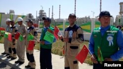 "Türkmenistanyň we Hytaýyň baýdaklaryny saklap duran işgärler. ""Galkynyş"" gaz gory, Türkmenistan. 4-nji sentýabr, 2013 ý."
