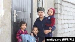 Вдова погибшего учителя Сеитжана Избасарова Амина Турганбаева с детьми у дверей арендуемого дома. Шымкент, 22 марта 2017 года.