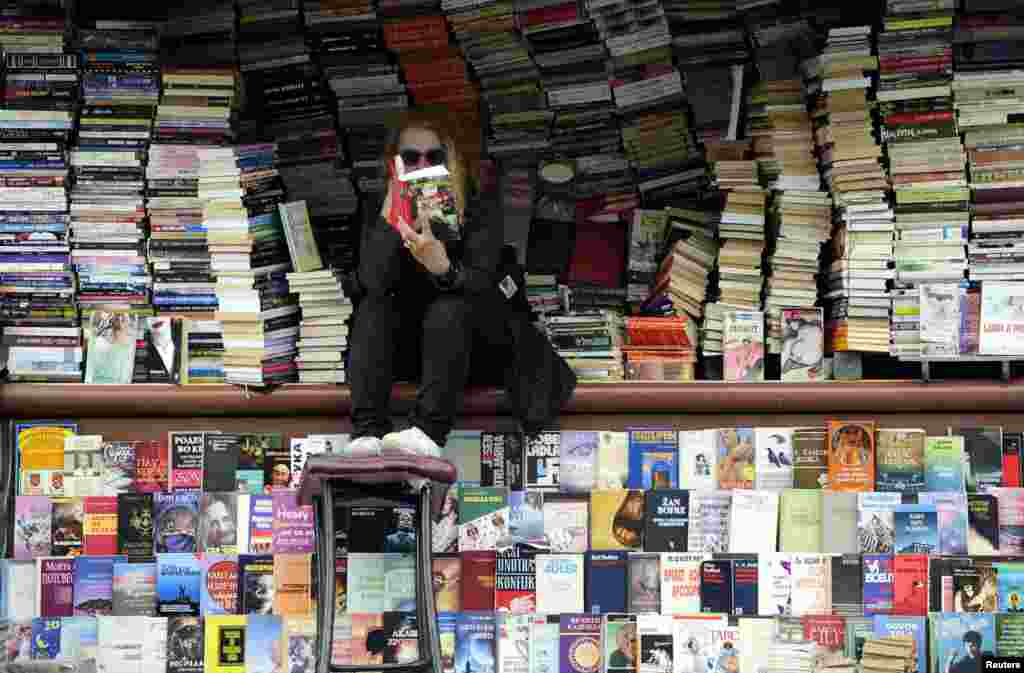 A woman reads at her open air book store in the Macedonian capital, Skopje, on April 24. (Reuters/Ognen Teofilovski)