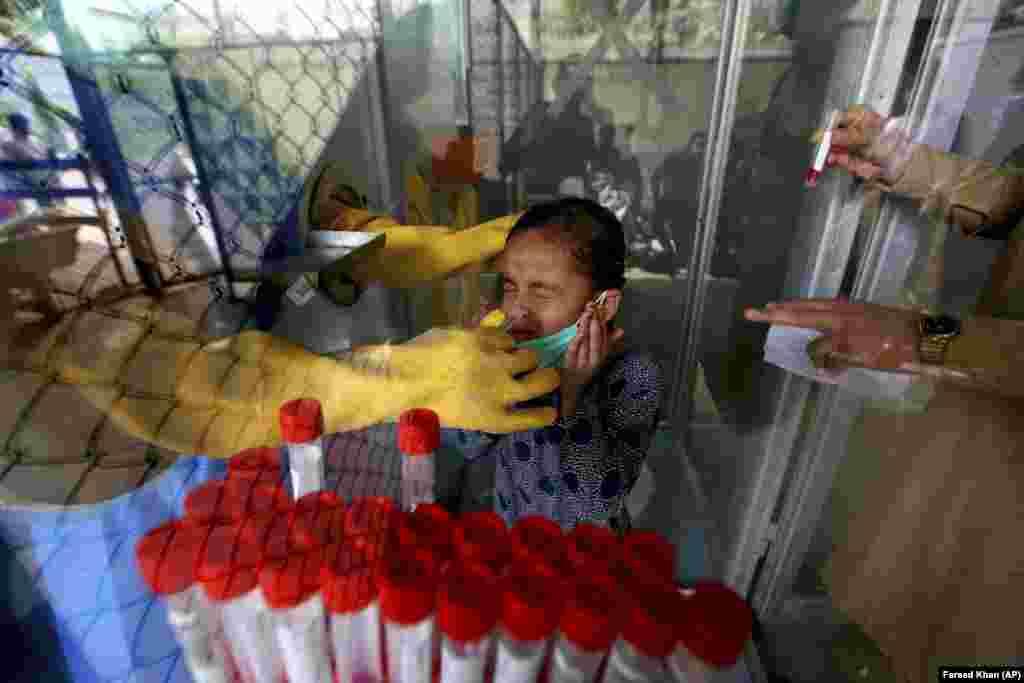 Медицинский работник берет мазок из носа пакистанки в центре тестирования COVID-19 в больнице в Карачи