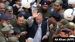 Police escort jailed former Pakistani prime minister Nawaz Sharif (C) as he leaves the accountability court in Lahore on October 11.