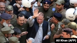 FILE: Police escort jailed former Pakistani prime minister Nawaz Sharif (C) as he leaves the accountability court in Lahore in October 2019.