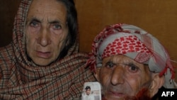 Pakistani Kashmir parents of convicted killer Shafqat Hussain, display a photograph of their son, in Muzaffarabad on March 12.