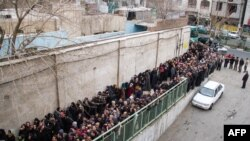 Low-income Iranians line up to receive food assistance in southern Tehran, Feb. 2014