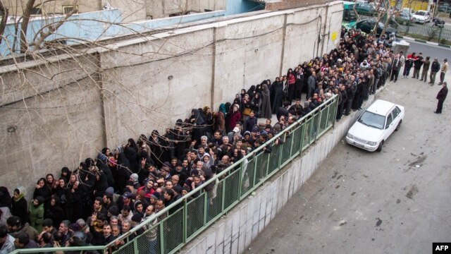 Iranians line up to receive food supplies in southern Tehran. Three people reportedly died while waiting in line in freezing temperatures, and hard-liners have alleged that the sight of citizens lining up for handouts is damaging to Iran's image abroad.
