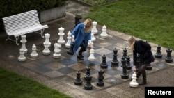 Російські журналістки, очікуючи на результати переговорів щодо іранської ядерної програми, грають гігантськими шахами у дворі Beau Rivage Palace Hotel у Лозанні, 1 квітня 2015 року