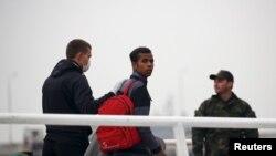 Oficir Fronteksa pomaže u deportaciji jednog od migranata iz Grčke na brod ka Turskoj