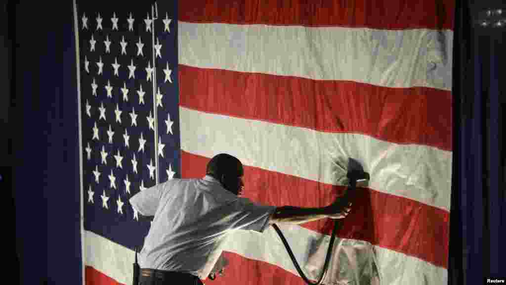 Hotel employee Denzil Telphia of Boston steams the wrinkles from an American flag hanging as a backdrop at the election night party for Democrat Elizabeth Warren, who won a seat in the U.S. Senate.