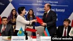 Mədəniyyət və Turizm naziri Əbülfəz Qarayev rəmzləri Qazaxıstan nümayəndəsinə təqdim edir.