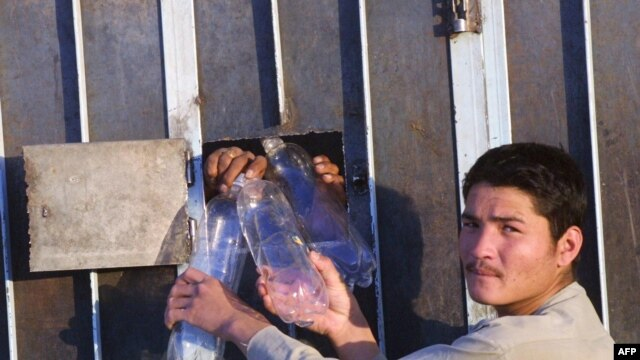 An Afghan man takes empty water bottles from Afghan men in Iranian detention in the southeastern Iranian city of Zahedan (file photo). Afghan officials say more than 5,600 Afghan nationals are in Iranian prisons for alleged drug crimes.