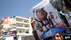 An Iranian man holds a poster bearing images of Israeli Prime Minister Benjamin Netanyahu, US President Donald Trump and Saudi King Salam during a parade marking al-Quds (Jerusalem) day in Tehran, June 23, 2017