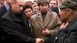 Russian President Vladimir Putin (left) shakes hands with an unidentified relative of a crew member of the Kursk, as Irina Lyachin (center), the wife of the commander of the submarine, looks on, in the town of Vidyayevo on August 22, 2000.