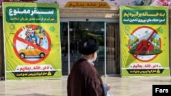 Large posters urge people to stay home and not travel in the city of Qom, a hotspot of coronavirus in Iran. March 28, 2020
