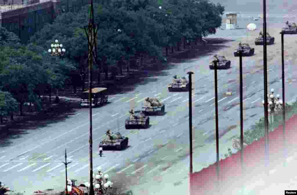 An unarmed man stands in front of a column of tanks on the Avenue of Eternal Peace on June 5. The tanks moved around him. The man's identity has not been confirmed and little is known about his fate after the standoff.