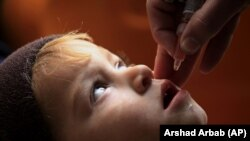 A health worker administers the polio vaccine to a child in Peshawar in December,