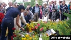 Керівник проекту «Не забудем, не простим» Анна Сорока покладає квіти загиблим. Фото «МИА Исток»